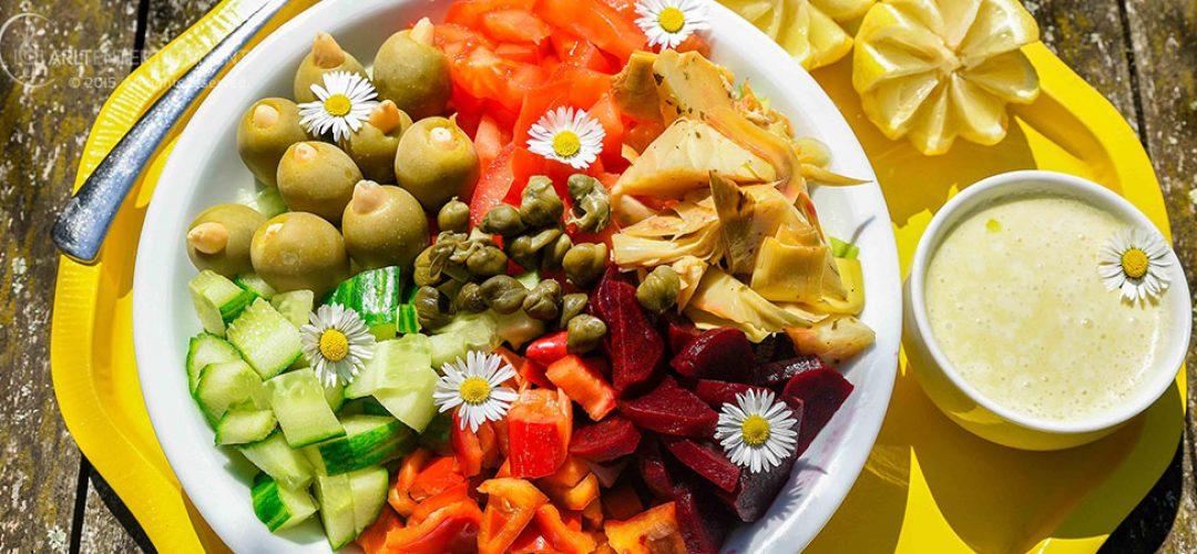 Salat in einer weißen Schüssel auf gelbem Tablett auf Holztisch