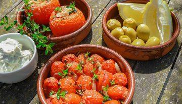 Gebratene Tomaten in einer irdenen Schüssel auf Holztisch