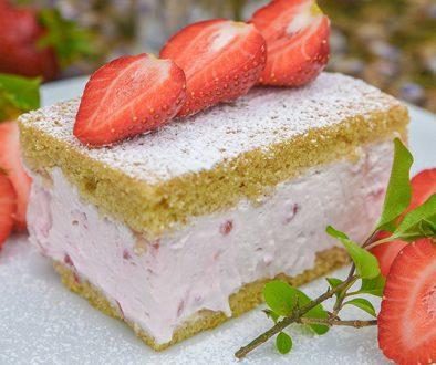 ErdbeerkäseSahne Torte auf einem weißßen Teller mit Flieder und Erdbeeren