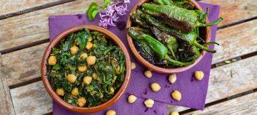 Kichererbsen mit Spainat in einer Schale daneben grüne Bratpaprika genannt Pimientos