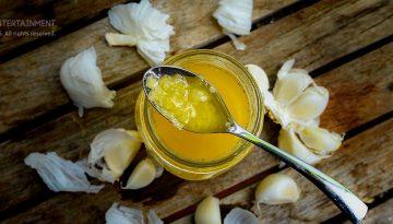 Knoblauch gepresst in Albaöl im Glas auf Holztisch