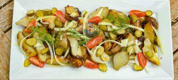 Topinambur mit sauren Gurken und Zwiebeln in einer Senfvinaigrette auf weisser Platte
