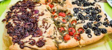 Focaccia mit Zwiebeln, Tomaten und Oliven.